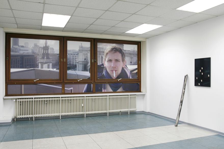 """Atelierausstellung bei Joscha Schell. An der Fensterfront klebt die Arbeit """"GREAT VIEWS WILL NEVER DIE"""", rechts daneben lehnt ein Fernmeldekabel Foto: Joscha Schell"""