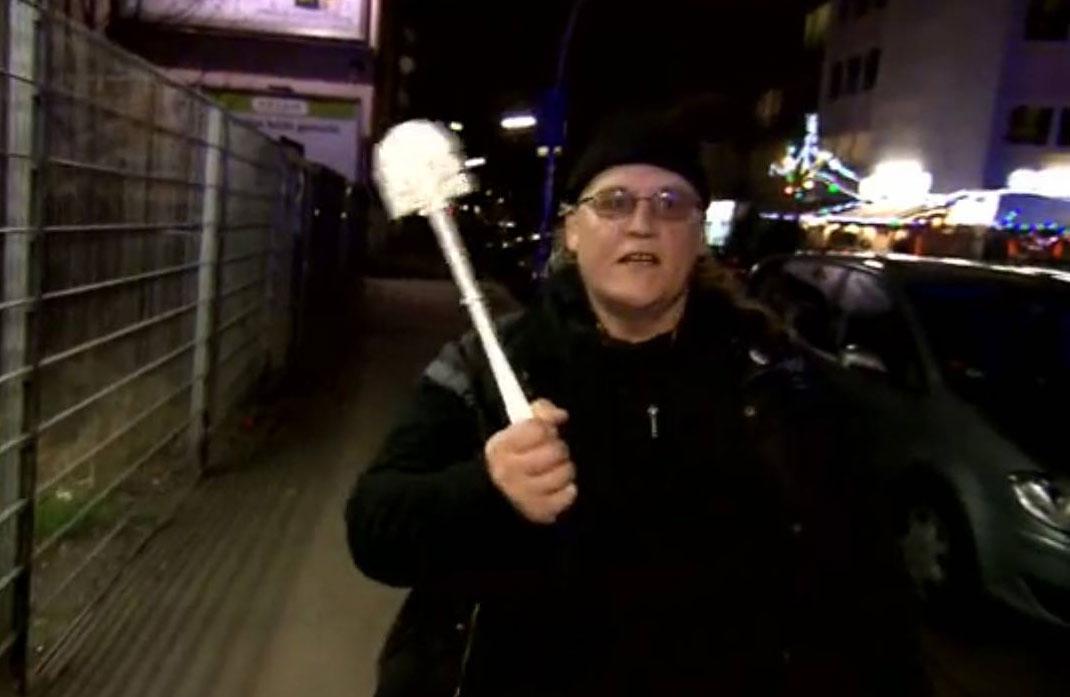 """Ein Anwohner bedroht die Staatsmacht mit einer """"Hamburger Klobürste"""" Foto: Spiegel TV"""